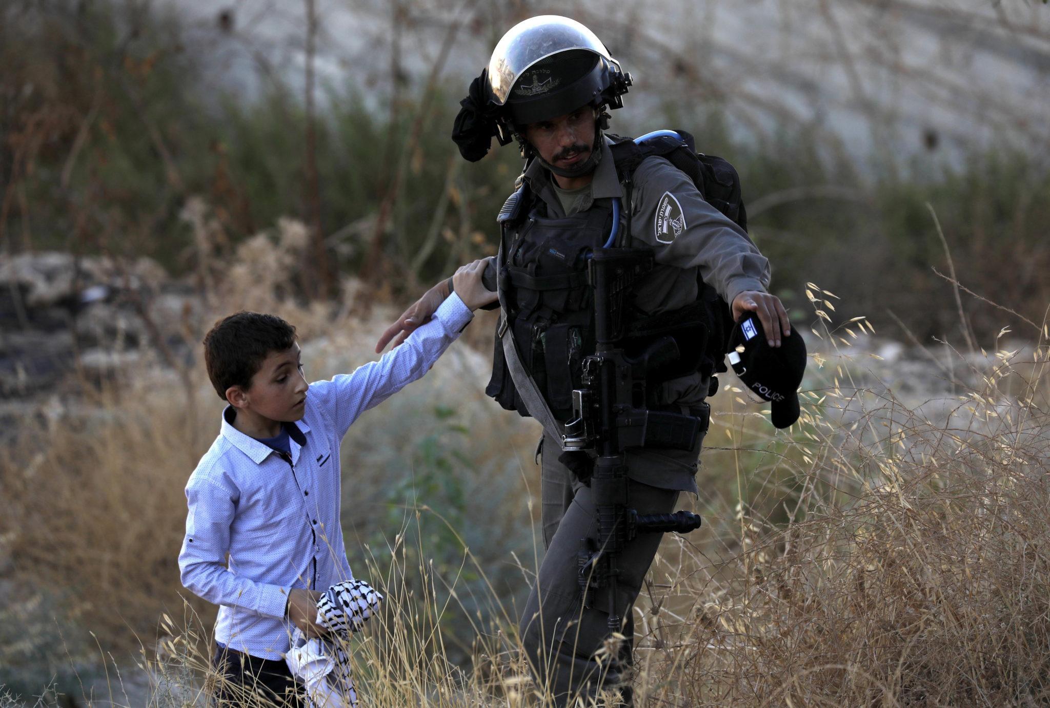 Palestyński chłopiec i izraelski żołnierz podczas rozbiórki w wiosce Sur Baher, która znajduje się po obu stronach izraelskiej bariery we Wschodniej Jerozolimie i na okupowanym przez Izrael Zachodnim Brzegu, fot. ABED AL HASHLAMOUN, PAP/EPA.