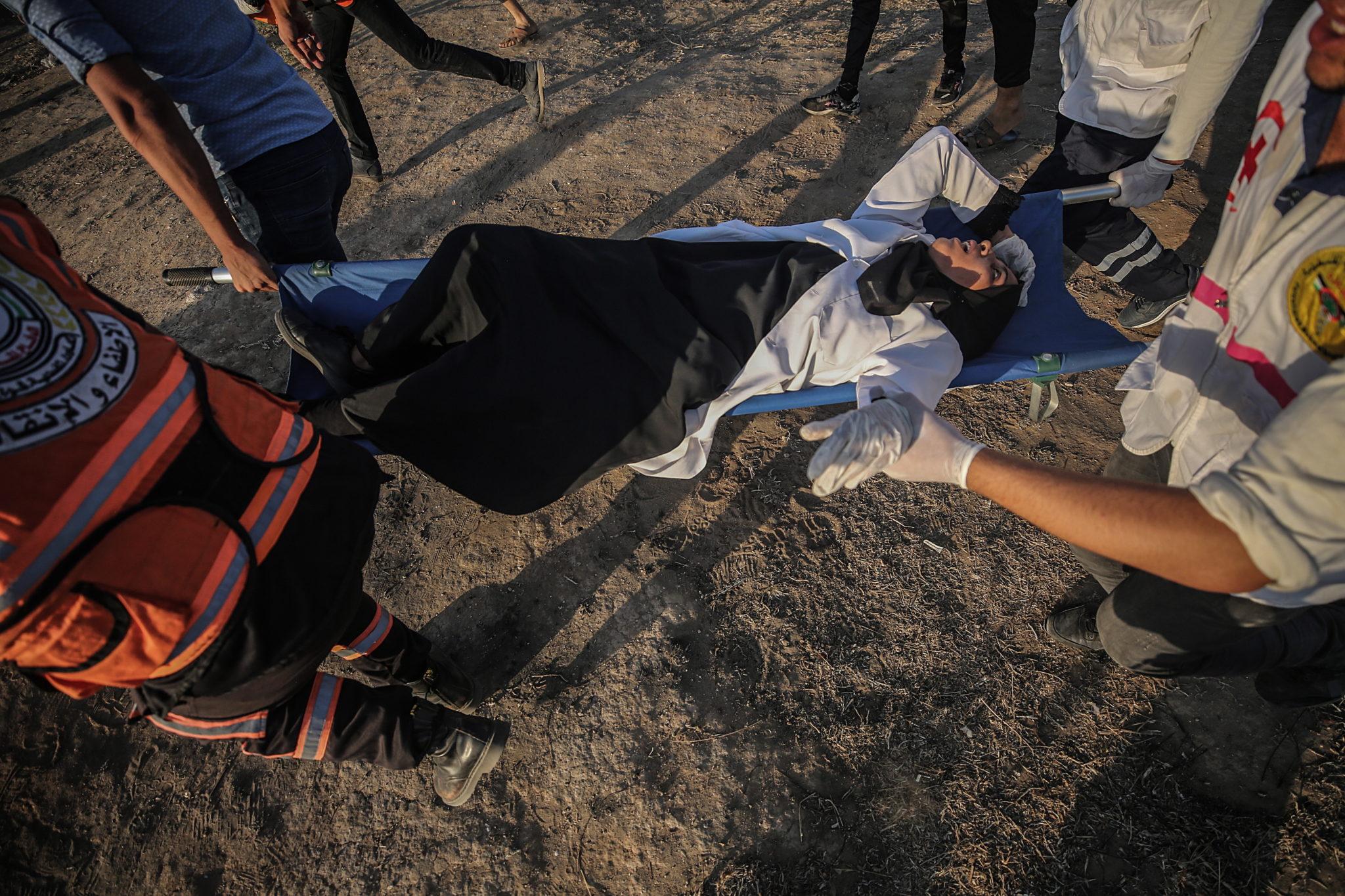 Palestyńska kobieta ranna podczas zamieszek w strefie Gazy. fot. EPA/MOHAMMED SABER