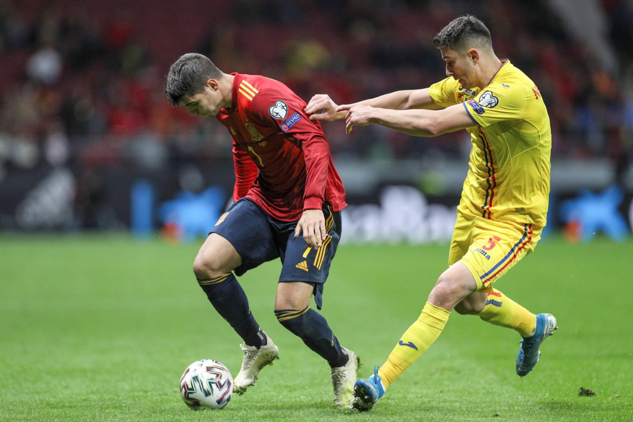 Alvaro Morata w akcji przeciwko reprezentantowi Rumunii Ionutowi Nedelcearu podczas meczu grupy F eliminacji UEFA EURO 2020 pomiędzy Hiszpanią a Rumunią na stadionie Wanda Metropolitano w Madrycie, fot.  EPA/RODRIGO JIMENEZ