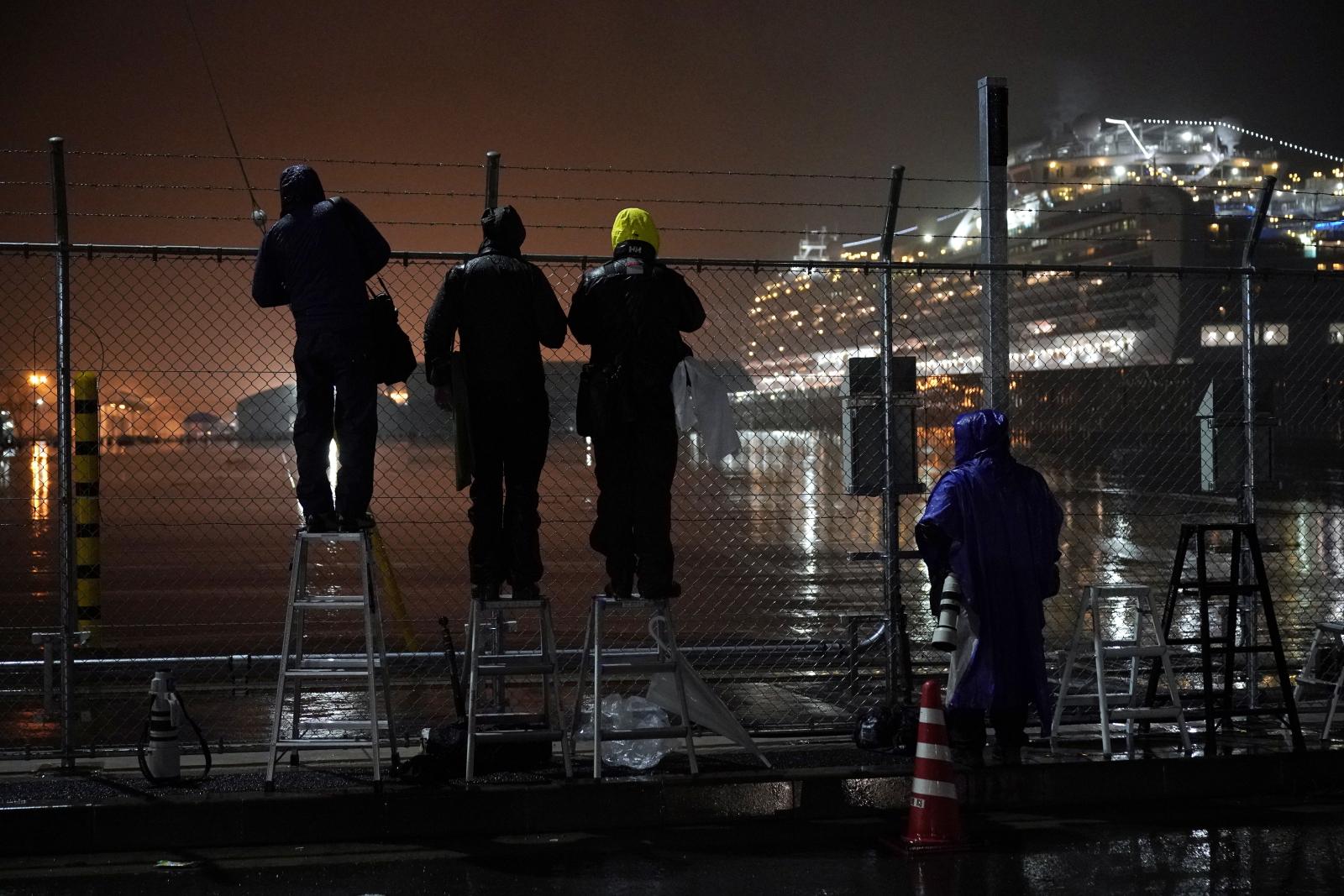 Reporterzy czekają na odjazd autobusów przewożących około 400 obywateli USA w celu repatriacji z terminalu statków wycieczkowych na molo Daikoku w Jokohamie, na południe od Tokio. Fot. EPA/FRANCK ROBICHON