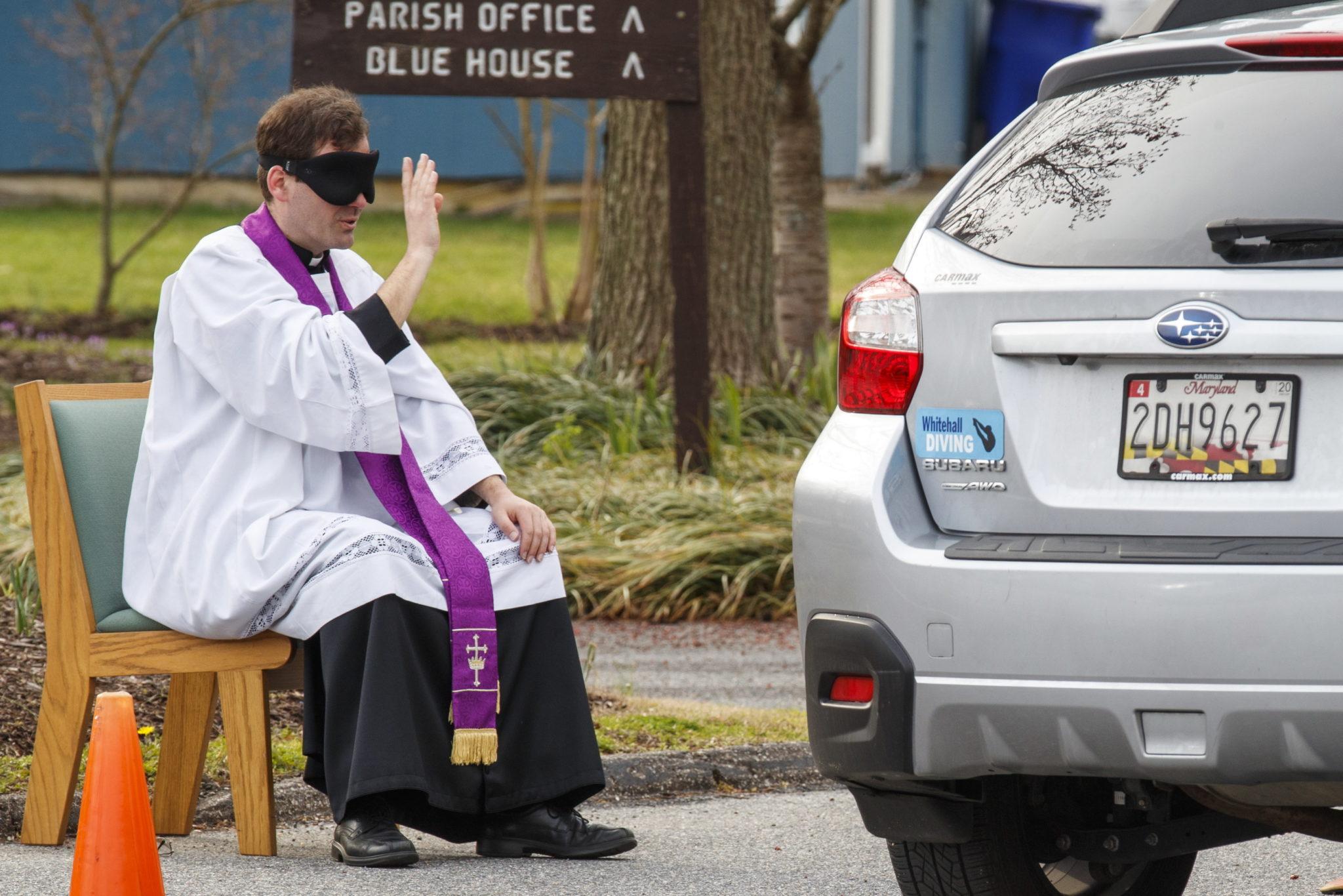 Ksiądz Scott Holmer spowiada swoich parafian podjeżdżających w samochodach.Bowie w Maryland, USA. fot. EPA/SHAWN THEW